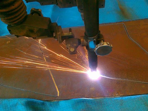 Her skjæres det ut sidevegger til gravemaskinskoffe med optisk plastmaskjærer.