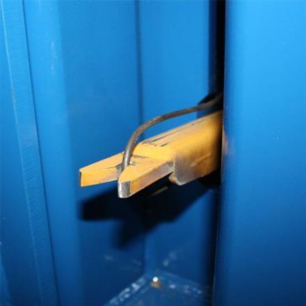 Klo som greppar tag i ståltråden som man binder balen med.