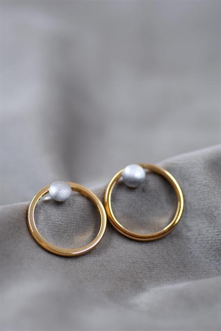 Två vigselringar som är omarbetade till örhängen. Detalj med knapp i vitguld.