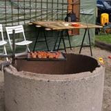 Roger reglerar värmen genom att samla kolen åt en sida och utnyttja att grillgallret kan vikas åt sidan.
