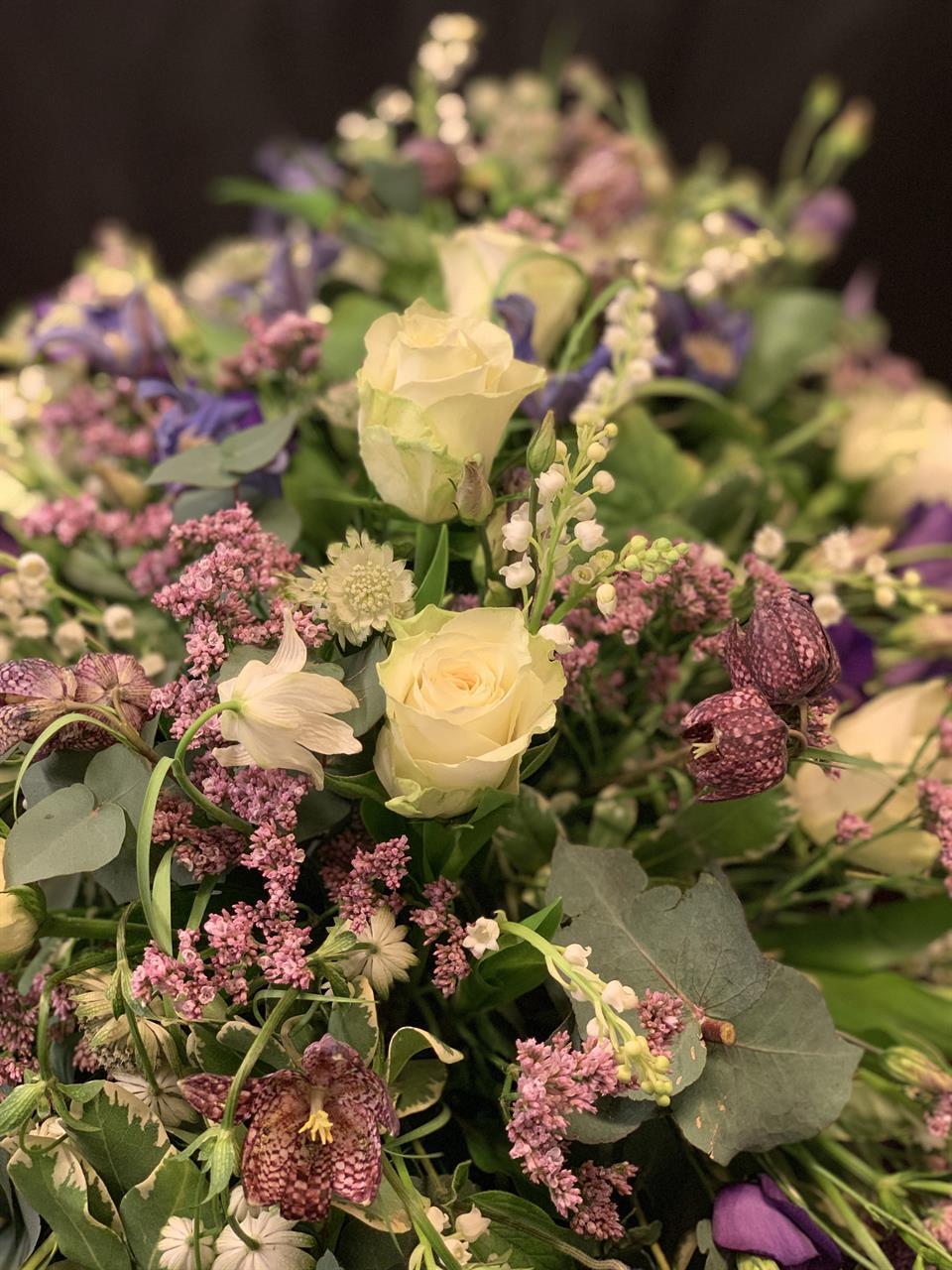 Närbild på kistdekoration i vårens färger och blommor