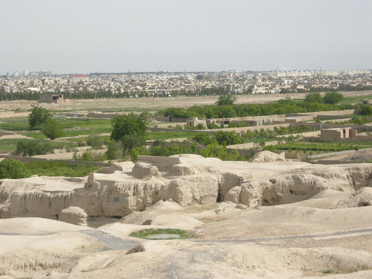 Utsikt fra de 4000 år gamle ruinene Teppe Sialk mot frukthager og boligstrøk i Kashan, Iran
