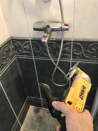 Mens sparkelen tørker, slisses eldre fuger på badet før nytt påføres