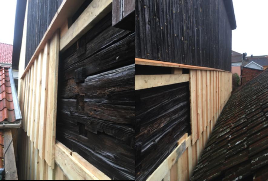 Bild 8. Panelningen gjordes från två håll pga närheten till intilliggande byggnader och pga av den pågående timmerlagningen. Panelen skarvades ungefär på mitten av panelbrädans längd. Panelväggen fick brytas för att klara väggens olika skevheter och utbuktningar i lod, samt utstickande knutkedjor och ändar på befintliga gängstänger. Överst sattes en droppnäsa uppemot befintlig pärlspontspanel i ca 15 graders lutning. Panelbrädorna sågades också i 15 grader i ovankant för att ansluta tätt till droppnäsan och likvärdigt i nedre ändan för att där skapa en droppnäsa.