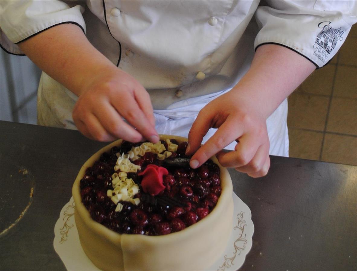 Här läggs den sista dekoren på en danskhallon tårta