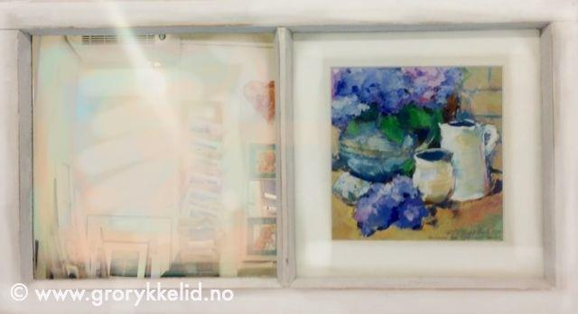 Speil med blomstermotiv i vindu