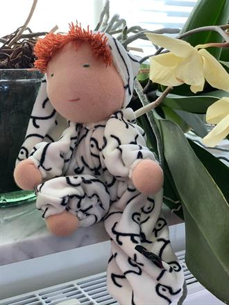 Middle sized hug doll with a hood and red hair. White velor with duck pattern - SEK 300!