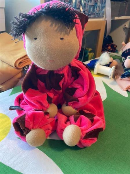 Stor kramdocka i ceriserosa med luva, svart hår och mörk hy