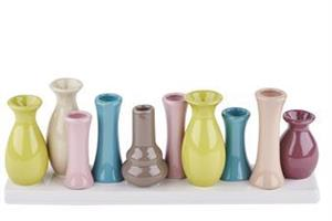 10 mini vaser på rad i olika färger.