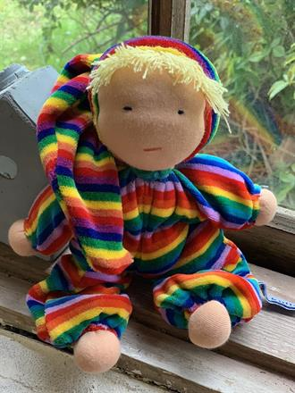 A middle sized waldorf doll, hug with a hood and blond hair