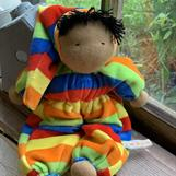 A middle sized Waldorf doll, with a hood, black hair and dark skin, ca 20cm long