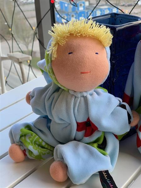 Mellanbarn i ljusblått med luva och blond lugg