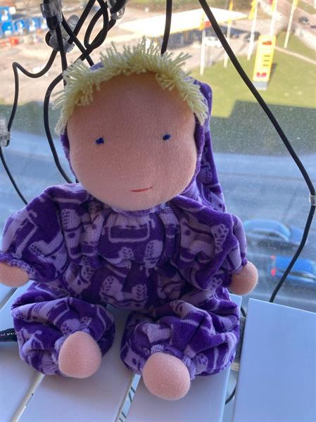 Mellanbarn i lila med luva och blond lugg