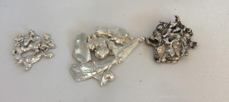 Tre bitar av smält silver.